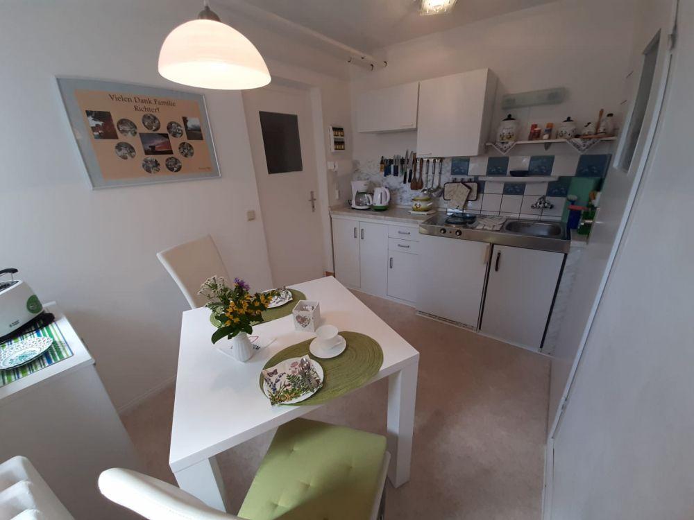 Küche mit 2-Platten-Herd, Kühlschrank mit Gefrierfach, Mikrowelle, Toaster, Wasserkocher, Kaffeemaschine, Radio, Geschirr und diversen Küchenutensilien, sowie Reinigungsmitteln und Geschirrtüchern